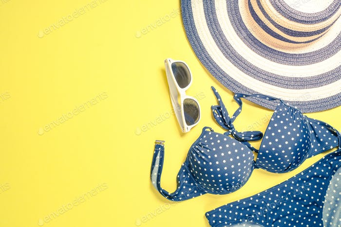 Summer travel vacation concept. Striped hat, swimsuit and sunglasses on yellow