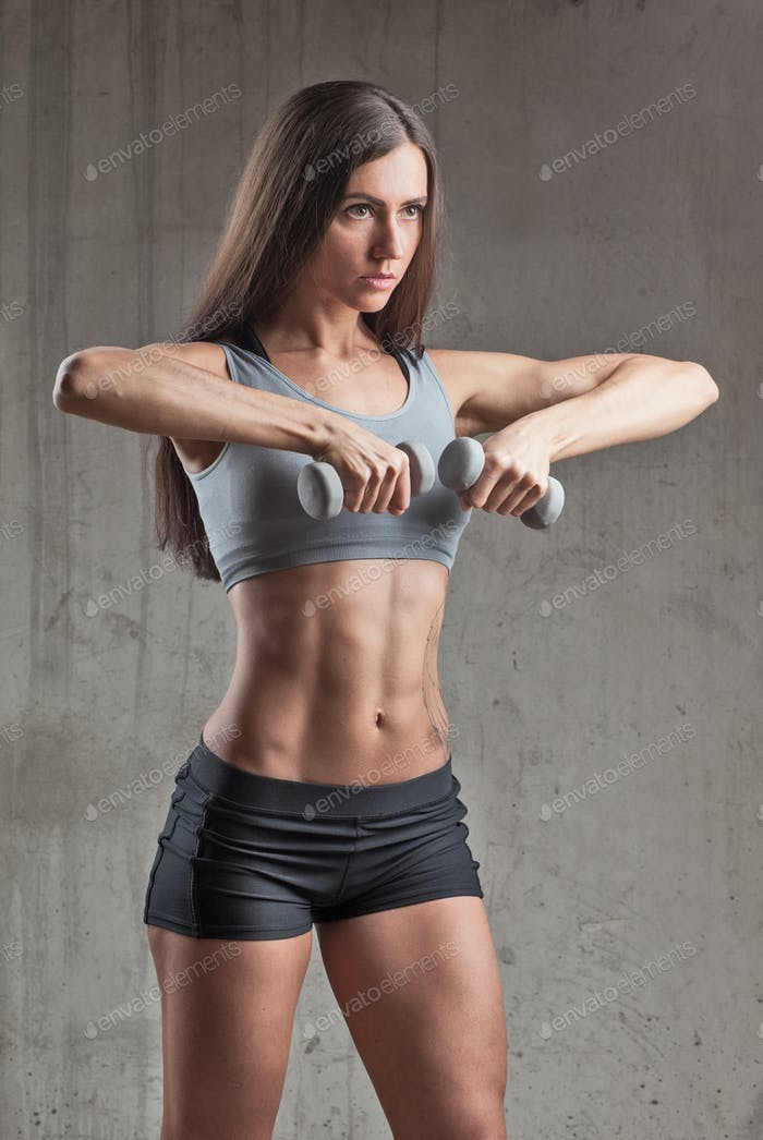 sporty woman with perfect body doing exercise with dumbbells