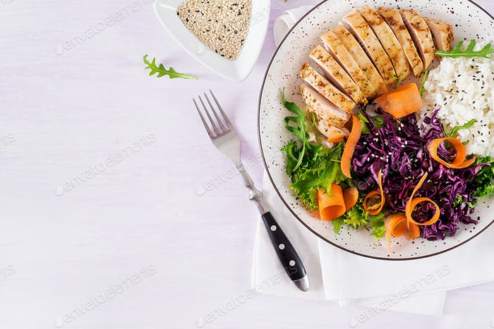 Buddha bowl dish with chicken fillet, rice,  red cabbage, carrot, fresh lettuce salad and sesame.