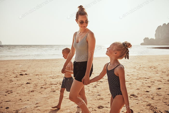 Smiling Mom and children walking together along a sandy beach