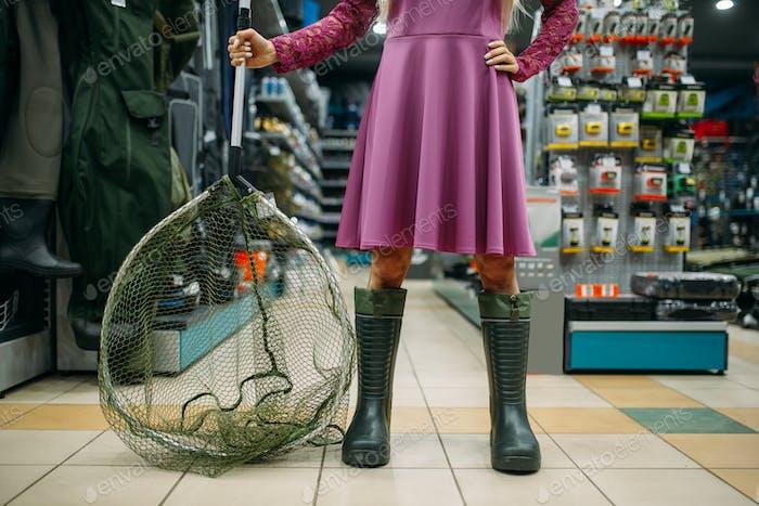 Fisherwoman in boots holds net in fishing shop