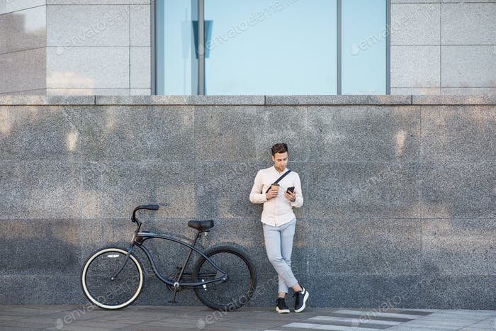 Online outdoors. Businessman with bicycle and cup of coffee, looks at smartphone leaning against the