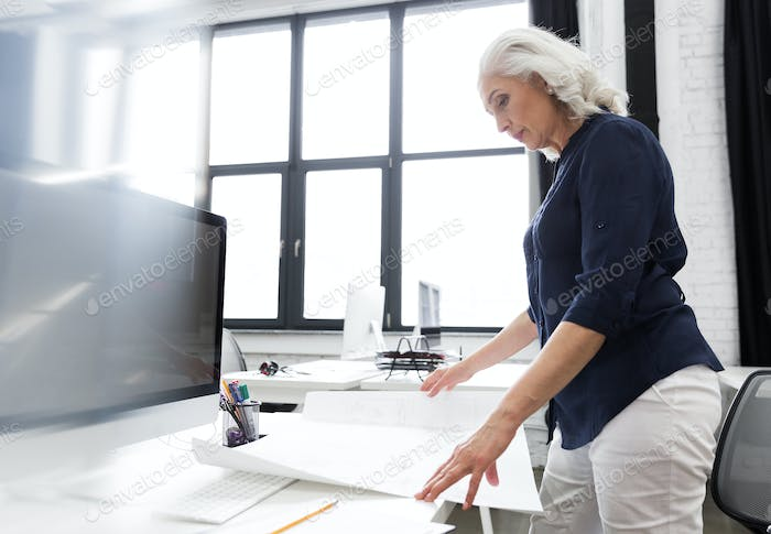 Mature business woman analyzing a chart held infront of her
