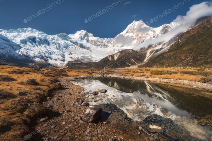 Beautiful view with high rocks with snow covered peaks, stones i