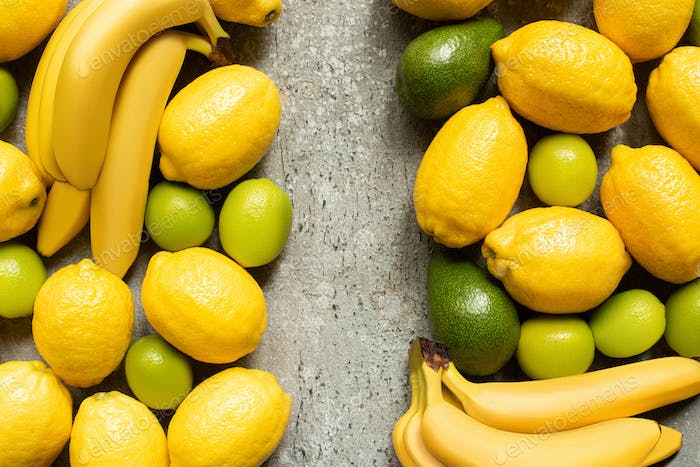 Top View of Colorful Bananas, Avocado, Limes And Lemons on Grey Concrete Surface