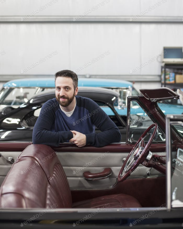 A portrait of a caucasian male leaving on the side of his classic car convertible in a repair shop.