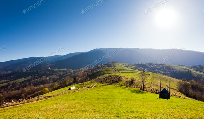 Green field with barn, mountains on background