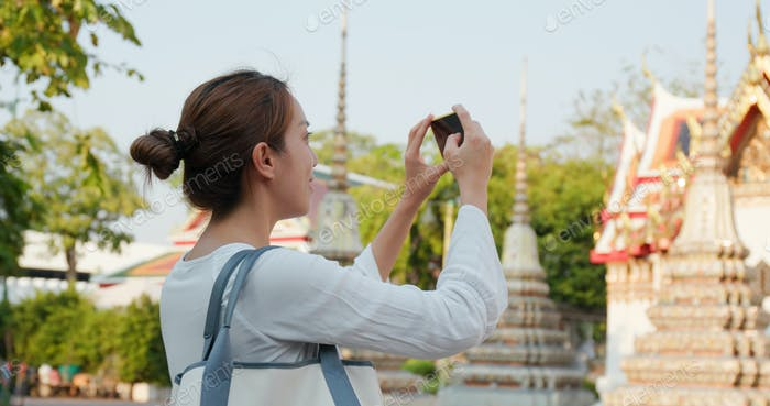 Woman take photo on cellphone at Thailand temple