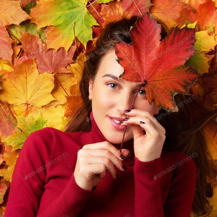 Mädchen mit rotem Ahornblatt in der Hand über bunte gefallene Blätter Hintergrund. Gold gemütliches Herbstkonzept