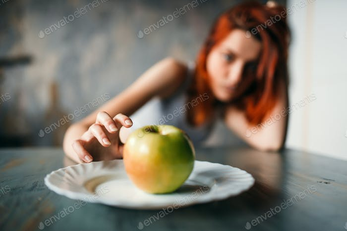 Female hand reaches plate with apple
