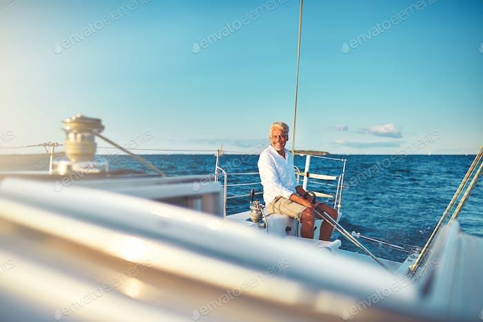 Smiling mature man sailing his yacht at sea