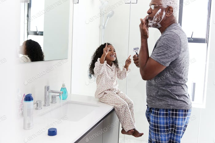 Grandfather Wearing Pajamas In Bathroom Shaving Whilst Granddaughter Watches