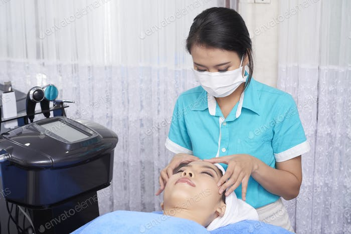 Professional spa worker giving face massage