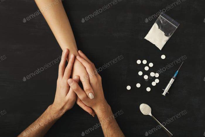 Drug addict hands on dark table