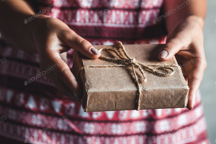 Female wearing a red with red christmas dress has a christmas gift in her hands