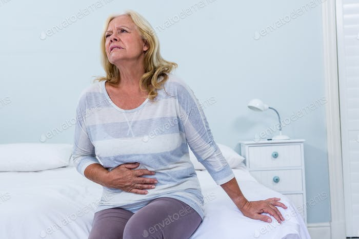 Woman sitting on her bed has stomach ache