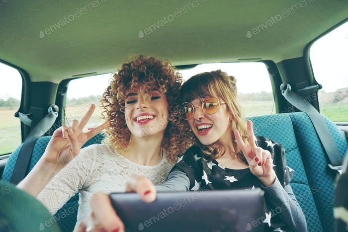 Two friends with their mobile phones in a road trip