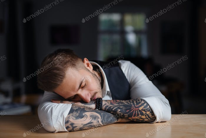 Tired young businessman sitting at the desk indoors in office, sleeping.