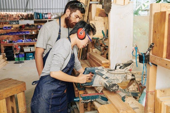 Woman cutting wood plank