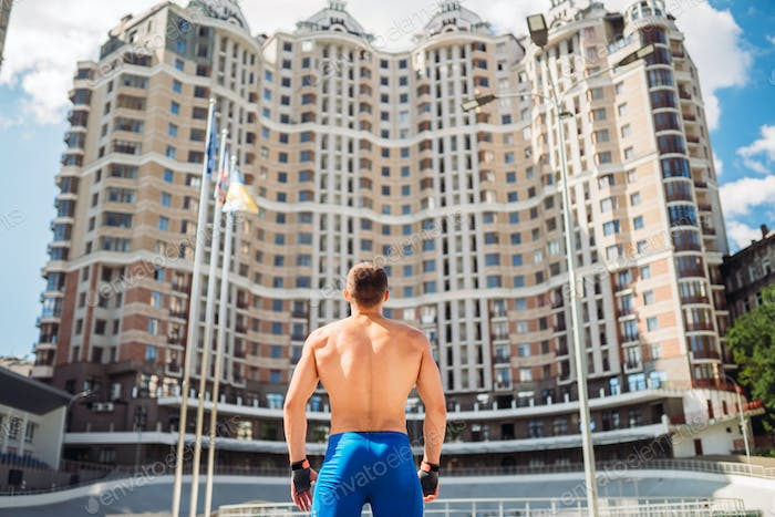 Muscular guy with a naked torso on the background of a tall building