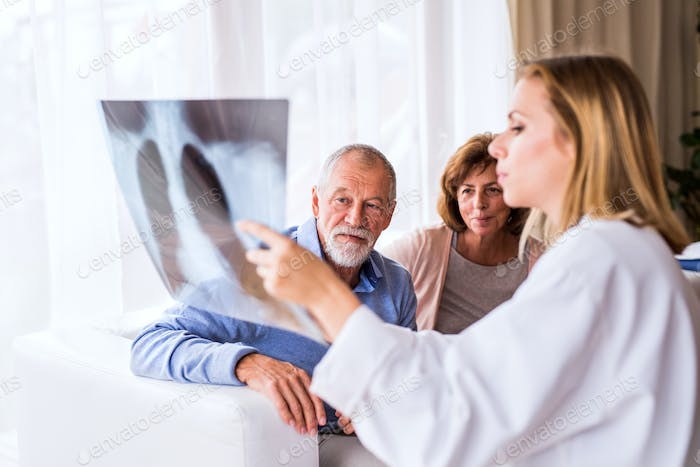 Female doctor with x-ray talking to a senior couple.