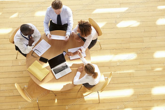 Four business colleagues in a team meeting, aerial view