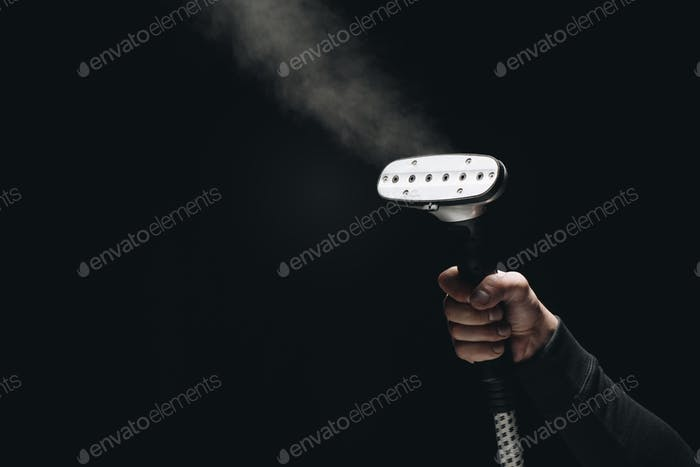 cropped shot of person holding garment steamer with steam on black
