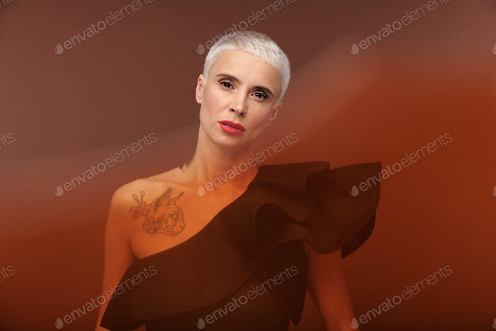 Elegant blond woman in black tanktop with tattoo on chest standing in isolation