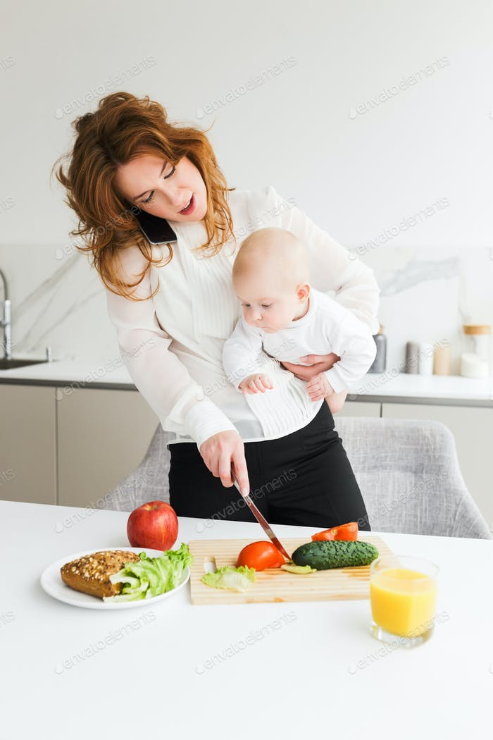 Young mother holding her little baby while talking on her cellphone and cooking on kitchen