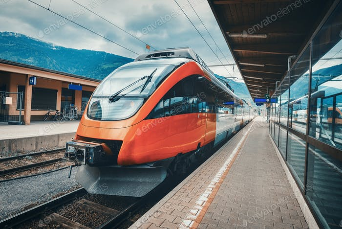 Hochgeschwindigkeitszug am Bahnhof in den Bergen bei Sonnenuntergang