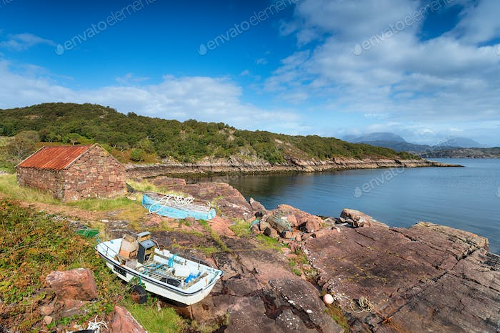 Old boats and a croft with a rusty tin roof on the shore at Kenm