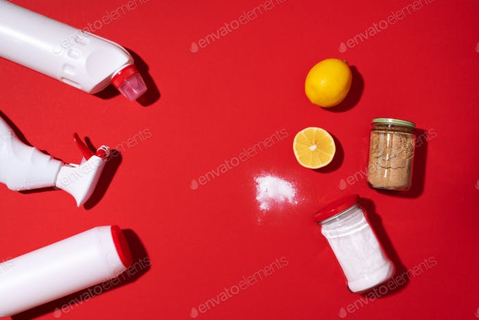 Baking soda, lemon and mustard powder against household chemicals products over red background. Top