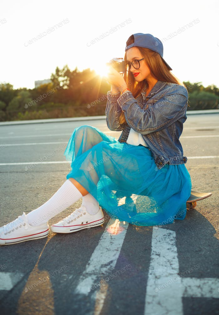 Summer lifestyle portrait of hipster girl with old camera