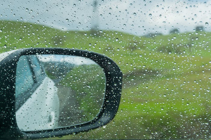 Drops of rain on the window and on the wing mirror