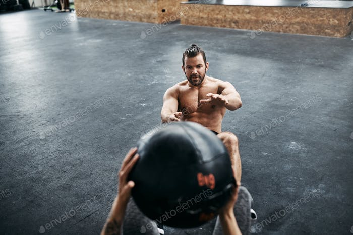 Fit people tossing a medicine ball at the gym