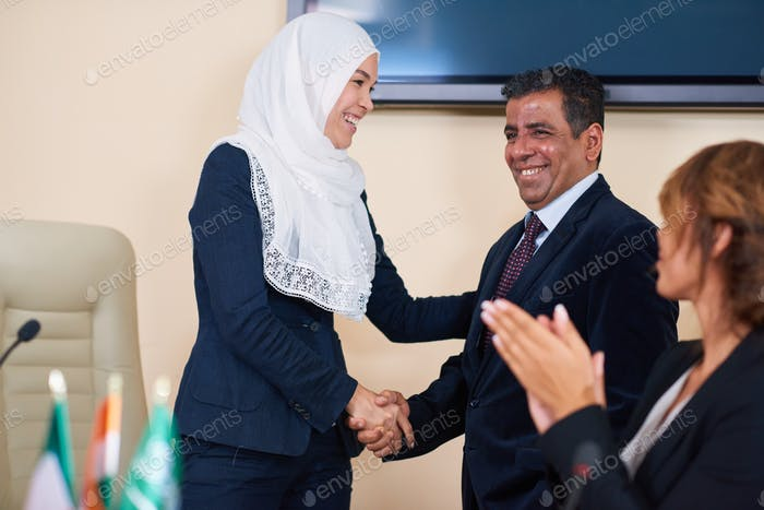 Happy young female delegate in hijab congratulating one of foreign speakers
