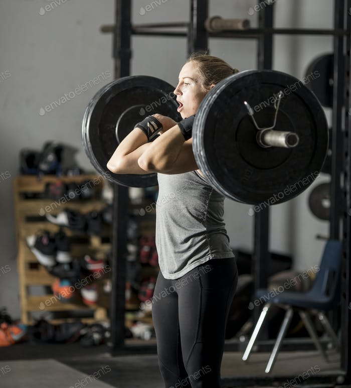 Strong young woman in gym struggling with heavy weights.