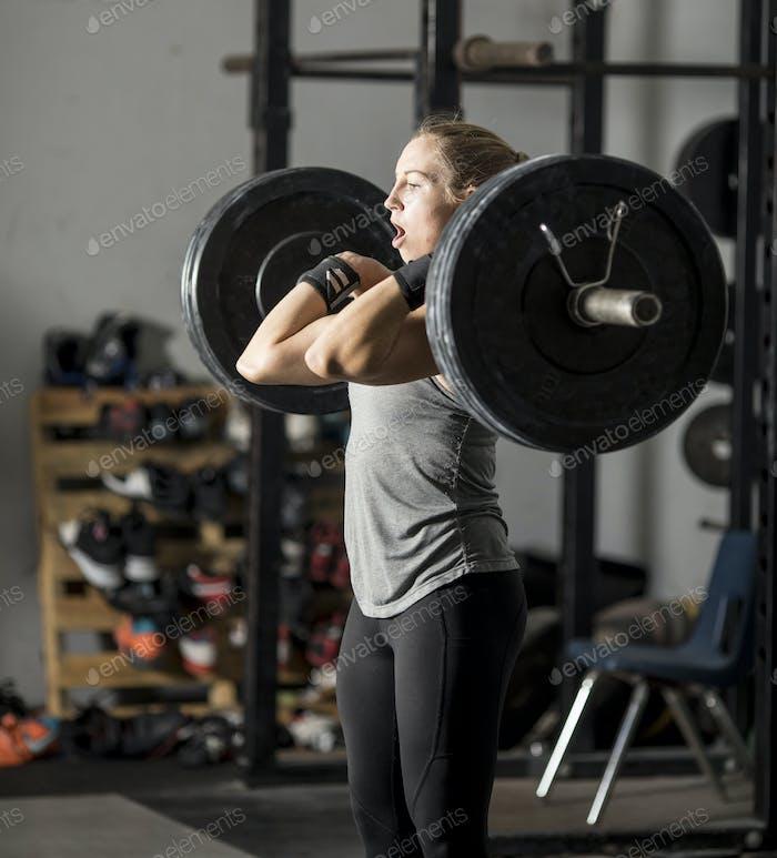 Starke junge Frau im Fitnessstudio kämpft mit schweren Gewichten.
