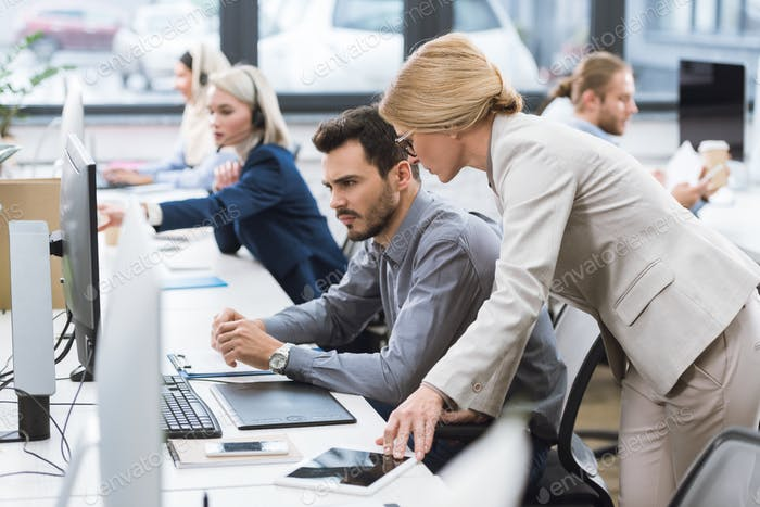 selektiver Fokus der Geschäftsfrau, die konzentrierten Kollegen bei der Arbeit am Arbeitsplatz im Büro hilft