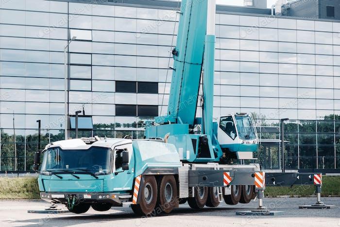 Ein großer blauer LKW-Kran steht bereit, auf hydraulischen Stützen auf einer Plattform neben einem großen