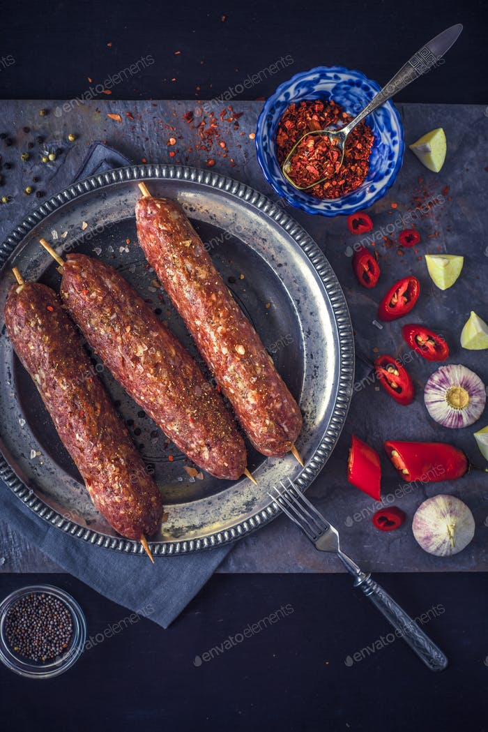 Raw kebabs with seasoning on the stone table vertical