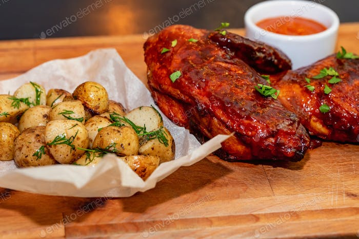 Smoked chicken thights served with potato and sauce on wooden tray close