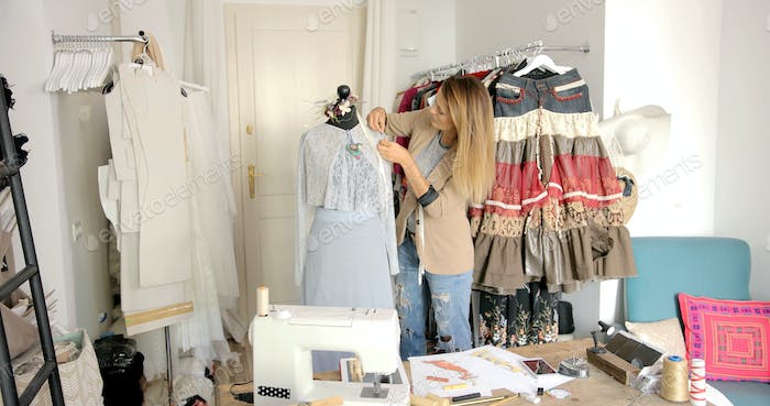 Dressmaker using mannequin for sewing beautiful dress