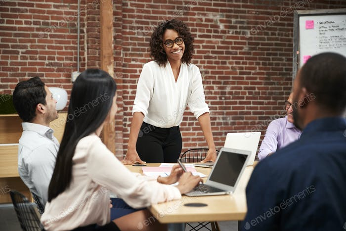 Businesswoman Standing And Leading Office Meeting Around Table