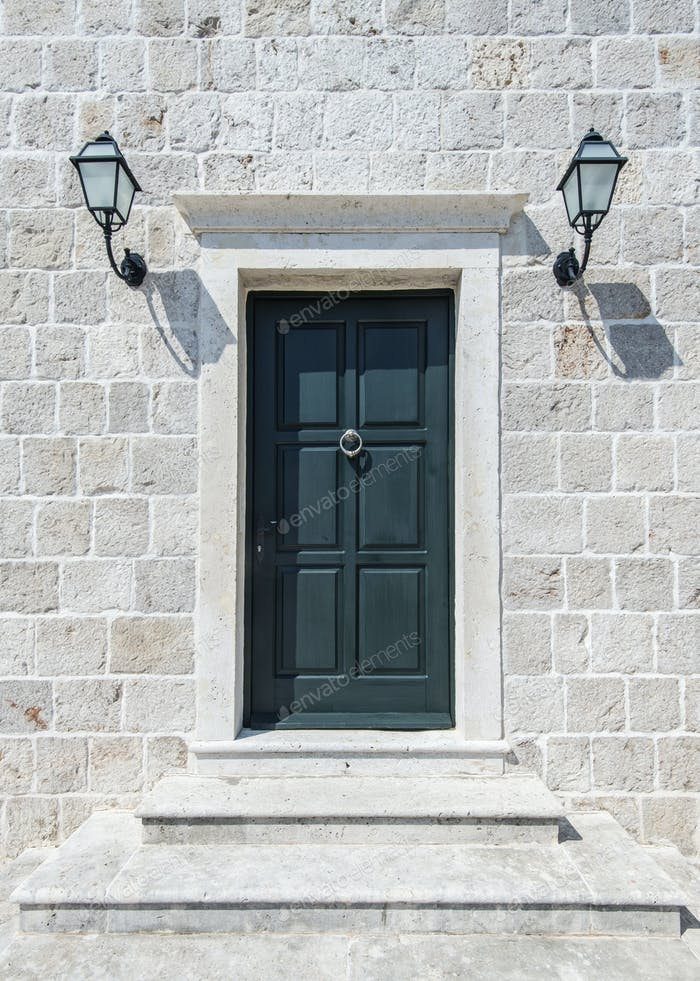 Front door and lamps of stone building