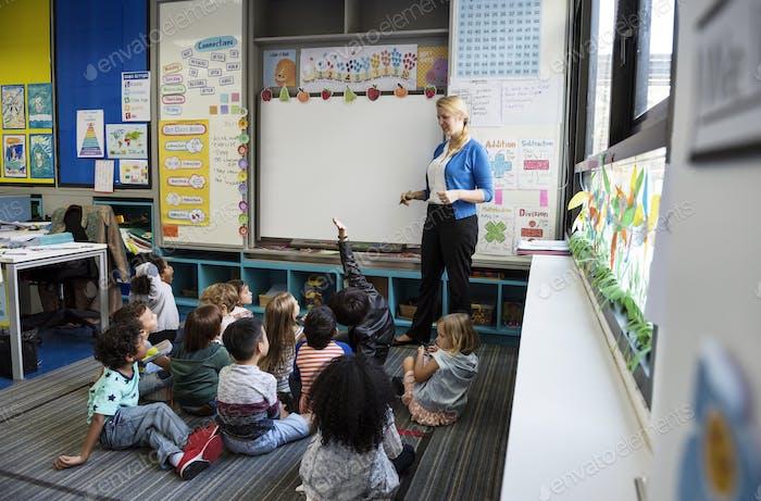 Kindergarten students sitting on the floor listening to teacher