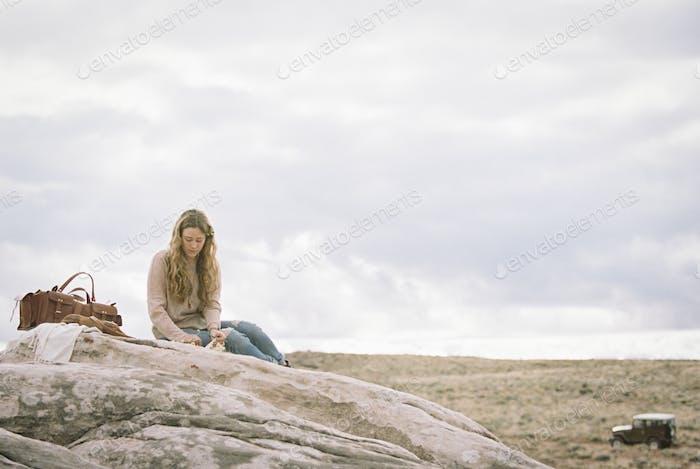 Frau sitzt auf einem Felsen, eine Ledertasche neben ihr.