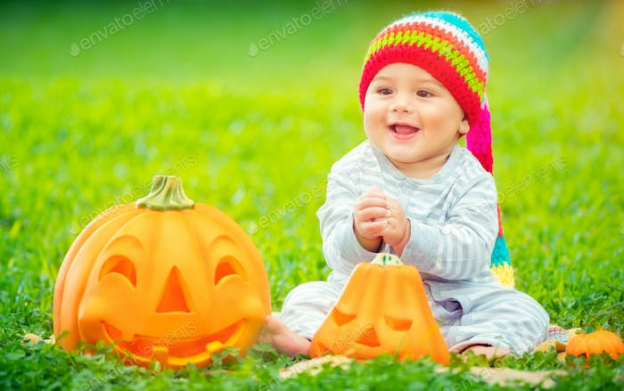 Cute baby with Halloween pumpkins