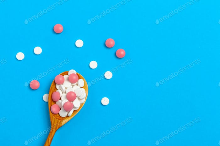 Multicolored pills in a spoon on a color background close up