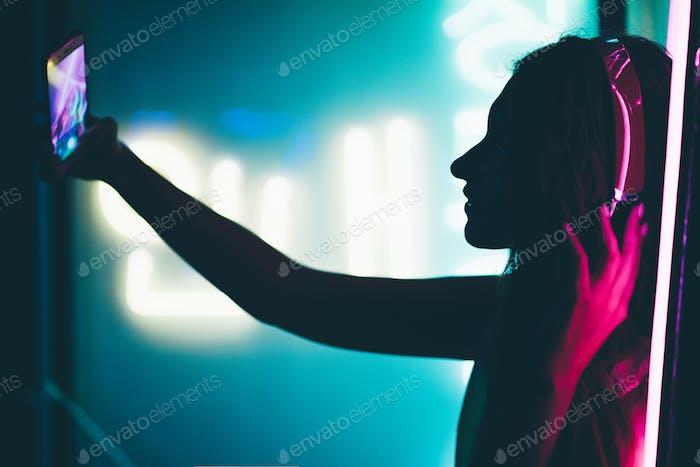 Fashion portrait of modern young woman making selfie.